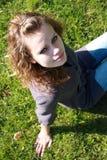 La fille s'assied sur une herbe verte Images stock