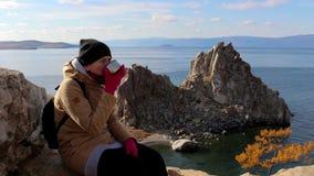 La fille s'assied sur une roche par la mer sur un fond de paysage étonnant, boit du thé banque de vidéos