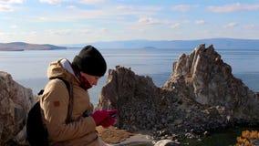 La fille s'assied sur une roche par la mer sur un fond de paysage étonnant, utilisations téléphonent clips vidéos