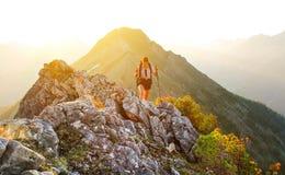La fille s'attaque en montagnes au coucher du soleil Photos stock