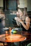 La fille s'est assise dans la fenêtre d'un café potable de café Photos stock
