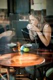 La fille s'est assise dans la fenêtre d'un café potable de café Photographie stock
