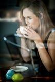 La fille s'est assise dans la fenêtre d'un café potable de café Photo stock