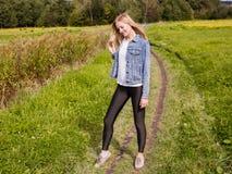La fille s'est habillée dans les guêtres et la veste de denim marchant sur la route de campagne images stock