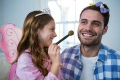 La fille s'est habillée dans un costume féerique appliquant le maquillage sur le visage de pères Photographie stock libre de droits