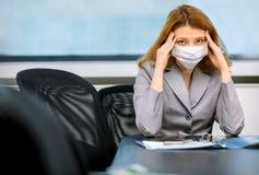 La fille s'est mise un infectieux au travail et s'assied dans le masque image libre de droits