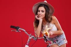 La fille s'est penchée son coude sur la roue d'une bicyclette sur un fond rouge Images stock