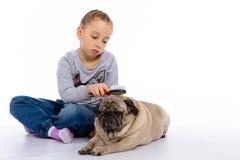 La fille s'inquiète du chien, écoute un stéthoscope Photos stock