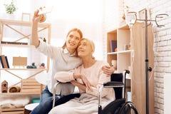La fille s'occupe de la femme agée à la maison Ils prennent le selfie au téléphone Image libre de droits