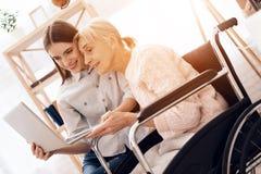 La fille s'occupe de la femme agée à la maison Ils utilisent l'ordinateur portable Image stock