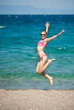 La fille sautant à la plage Images libres de droits