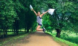 La fille sautant avec des sacs de déchets après plogging image libre de droits