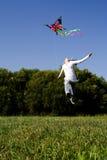La fille sautant avec le cerf-volant Images libres de droits