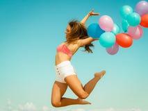 La fille sautant avec les ballons colorés sur la plage Photo libre de droits