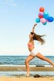 La fille sautant avec les ballons colorés sur la plage Image stock