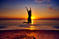 La fille sautant dans le ciel photo stock