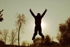 La fille sautant dans le coucher de soleil photographie stock libre de droits