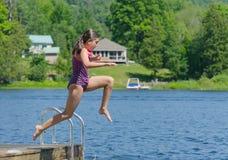 La fille sautant dans le lac outre du dock au cottage photographie stock