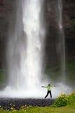 La fille sautant devant la cascade à écriture ligne par ligne Photos libres de droits