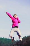La fille sautant en parc Photos stock
