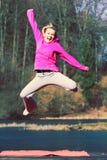 La fille sautant en parc Photographie stock