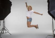 La fille sautant sur l'ensemble d'un photoshoot Images libres de droits