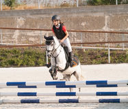 La fille sautant sur le poney rouan au-dessus de l'obstacle Image stock