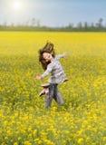 La fille sautant sur le pré Photo stock