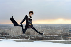 La fille sautant sur le toit dans la ville Photos stock
