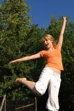 La fille sautant sur le tremplin Photo stock