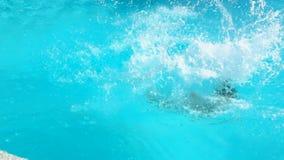 La fille saute dans l'eau avec un tour banque de vidéos