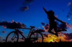 La fille saute, vélo au coucher du soleil Images libres de droits