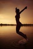 La fille sautent en rivière au coucher du soleil image stock