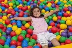 La fille se couchent dans une piscine en plastique colorée de boule Photos stock