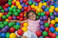 La fille se couchent dans une piscine en plastique colorée de boule Photos libres de droits
