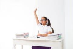 La fille se lèvent sa main dans la chambre de classe Image stock