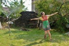 La fille se réjouit dans l'éclaboussure de l'eau dans le jardin photos stock