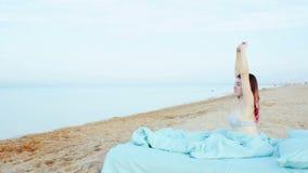 La fille se réveille sur la plage banque de vidéos