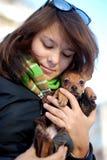 La fille se retient sur des mains d'un chiot préféré Photos libres de droits