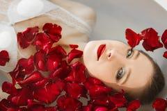 La fille se situe dans la salle de bains avec des pétales de rose Un bain de bien-être avec des roses image libre de droits
