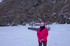 La fille se tenant à côté d'un aéroglisseur à la roche sur le Baikal Photos libres de droits