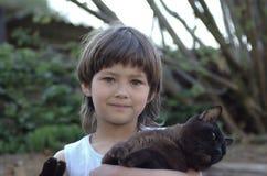 La fille se tenant dans des ses bras brunissent le chat birman Photos stock