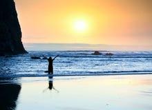 La fille se tenant dans les vagues, bras a augmenté au ciel au coucher du soleil Photo stock