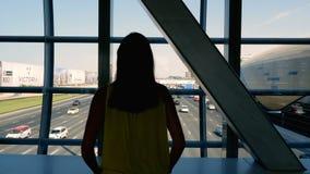 La fille se tient à la station de métro, dans le passage, regardant les mouvements du trafic le long d'une route urbaine à grand  banque de vidéos