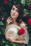 La fille se tient contre des buissons d'un fond avec les roses rouges photos libres de droits