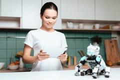 La fille se tient dans la cuisine et tient un comprimé Un petit robot de rhinocéros se repose à côté de la table Photos stock