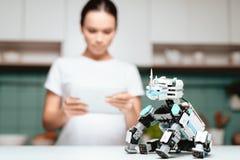 La fille se tient dans la cuisine et tient un comprimé Un petit robot de rhinocéros se repose à côté de la table Photos libres de droits