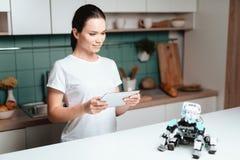 La fille se tient dans la cuisine et tient un comprimé Un petit robot de rhinocéros se repose à côté de la table Images stock