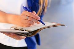 La fille se tient dans des mains journal intime, carnet avec des feuilles et stylo et acte judiciaire photographie stock