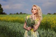 La fille se tient dans un domaine À l'arrière-plan, fleurs jaunes image libre de droits